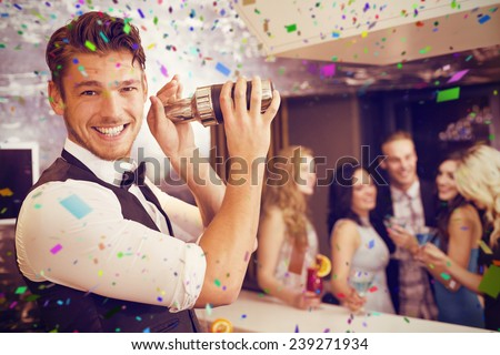 Handsome barman smiling at camera making a cocktail against flying colours - stock photo