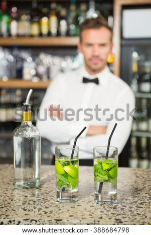 Handsome barman standing behind cocktails in a pub - stock photo