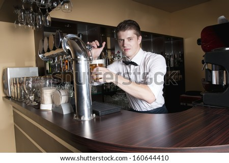 Handsome bartender in white shirt serving beer in front of the bar.  - stock photo