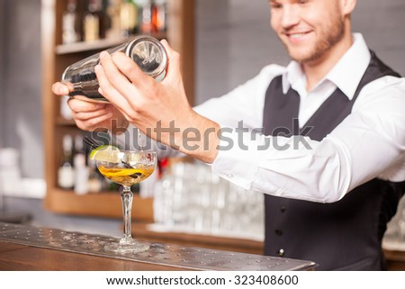 Handsome bartender is making cocktail in bar. He is holding shaker and poring beverage into glass. The man is looking at cocktail with inspiration. He is standing and smiling - stock photo