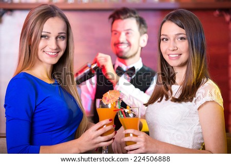 Handsome bartender serving cocktail to attractive woman in a classy bar