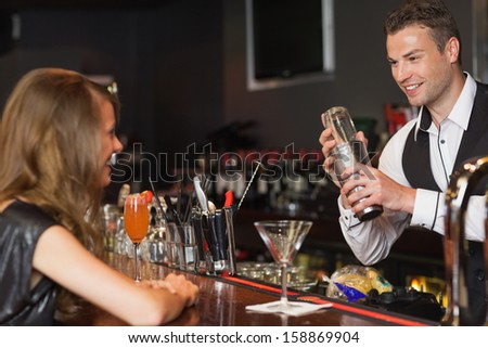 Handsome bartender serving cocktail to beautiful woman in a classy bar - stock photo