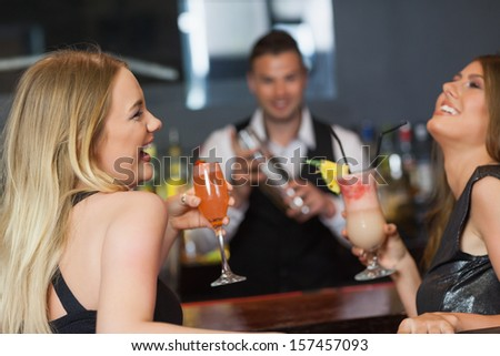 Handsome bartender working while gorgeous friends having cocktails in a classy bar
