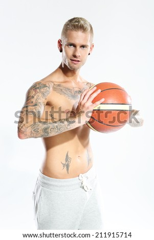 Handsome basketball player  Attractive young boy with an orange ball for basketball, tattooed in sports trousers  - stock photo