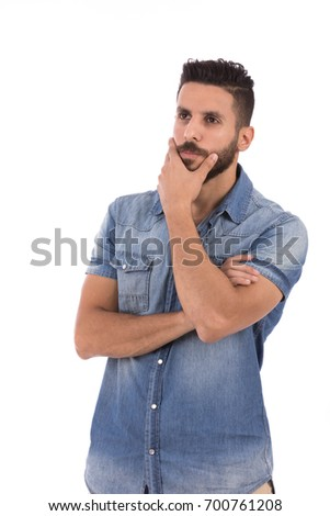 Handsome beard young man thinking and holding his chin, guy wearing jeans shirt, isolated on white background