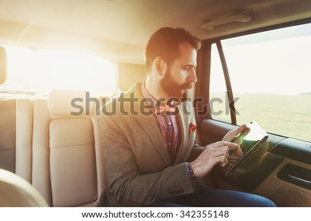 handsome bearded businessman sitting on back seat of car and touching digital tablet pc - stock photo