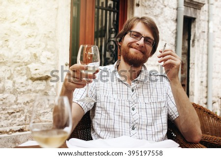 Handsome Bearded European Man Drinking Wine and Smoking Cigarette Sitting in Street Cafe.  - stock photo
