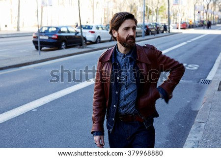 Handsome bearded man dressed in cool clothes walking on the street near roadside in warm autumn season, adult modern male in leather jacket strolling in the city during recreation time in weekend - stock photo