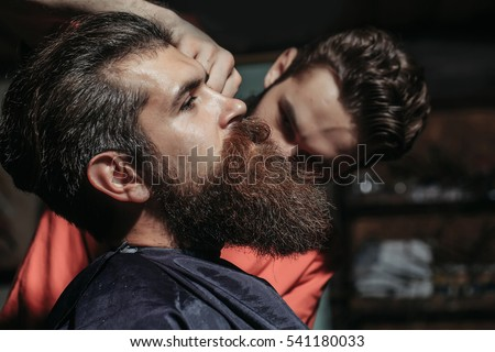 Handsome bearded man, hipster, brunette with beard and moustache has haircut or clippering in hairdressing saloon. Barber works in barbershop