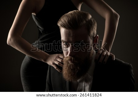 handsome, bearded man in a studio with female hands, portrait.