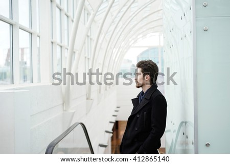 Handsome bearded man in black stylish coat looking away while standing in modern building - stock photo