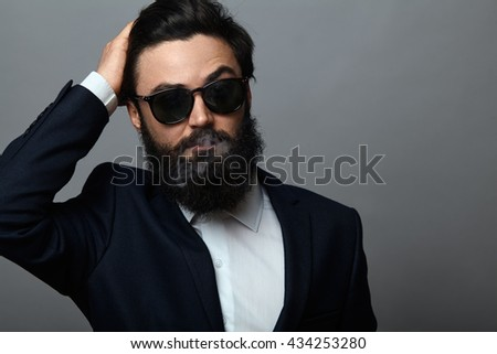 handsome bearded man in black suit and sunglasses posing against grey background. Confident serious business man fixing hair and smoking - stock photo