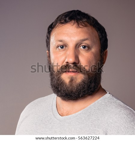 Handsome bearded man in gray t-shirt looking at camera.