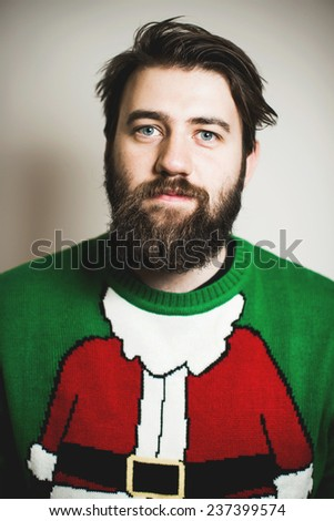 Handsome bearded man in stylish Santa Claus pullover smiling at Christmas and New Year party - stock photo