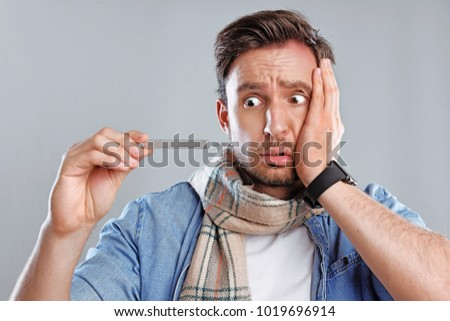 Handsome bearded man is sick isolated on a white background. Sad concerned guy in a scarf is ill and looks at the thermometer, he has a temperature