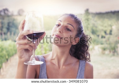 handsome bearded man looking glass of wine before drinking