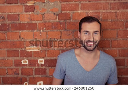 Handsome bearded man posing against a red brick wall in a casual t-shirt smiling at the camera with copyspace alongside - stock photo