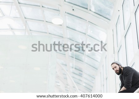 Handsome bearded man sitting on window sill while looking at camera. Geometric interior with glass ceiling