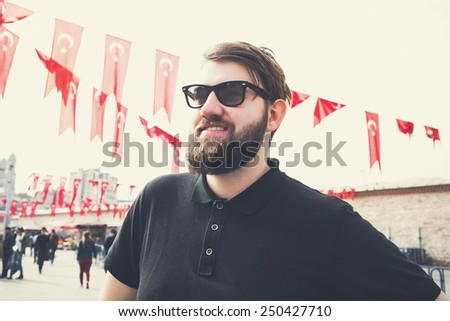Handsome bearded man smiling near turkish flags at Taksim Square in Istanbul, Turkey - stock photo