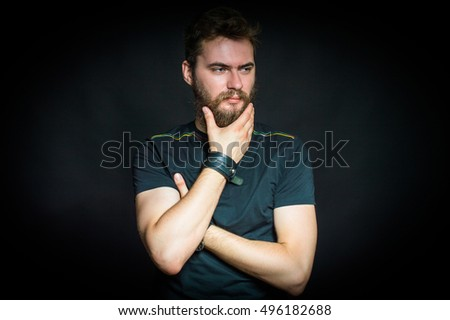 Handsome bearded man standing. On a black background.