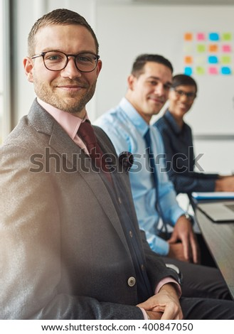 Handsome bearded man wearing suit and tie with two management colleagues in meeting at conference table in front of large white board - stock photo