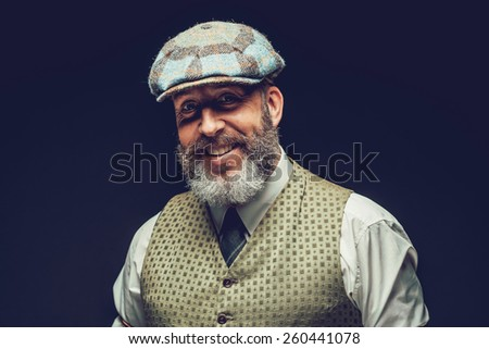 Handsome bearded man with a lovely smile wearing a cloth cap and waistcoat standing looking at the camera, head and shoulders on black - stock photo