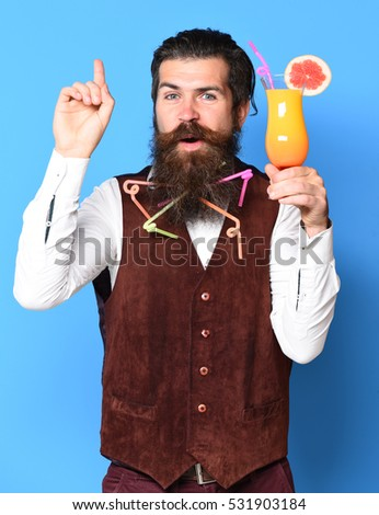 handsome bearded man with colorful tubes in long beard and mustache has stylish hair on satisfied face holding glass of alcoholic cocktail in vintage suede leather waistcoat on blue studio background