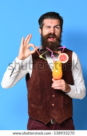 handsome bearded man with colorful tubes in long beard and mustache has stylish hair on smiling face holding glass of alcoholic cocktail in vintage suede leather waistcoat on blue studio background