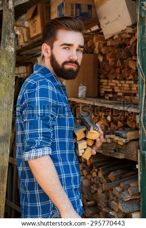 Handsome bearded man with firewoods