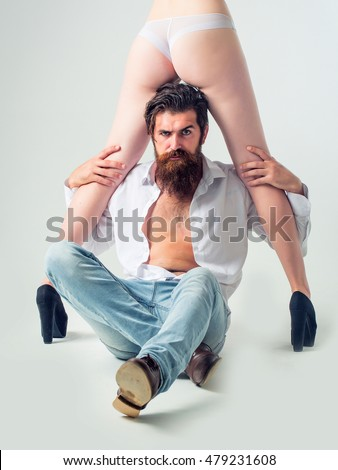 handsome bearded man with long beard and moustache on serious face sitting near sexy female legs and buttocks in lingerie and shoes of young pretty girl in studio isolated on white background