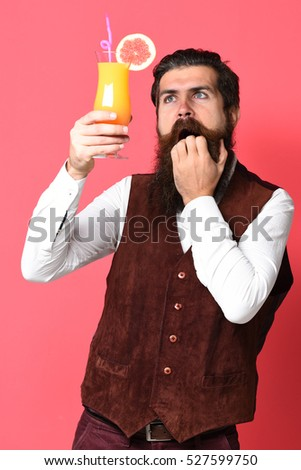handsome bearded man with long beard and mustache has stylish hair on surprised face holding glass of alcoholic cocktail in vintage suede leather waistcoat on red studio background