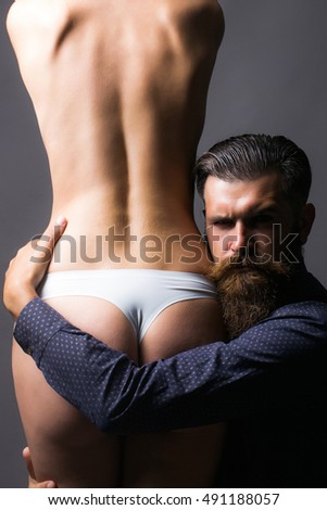 handsome bearded man with long beard on serious face embracing young woman with sexy body legs and buttocks with bare back in lingerie on grey background