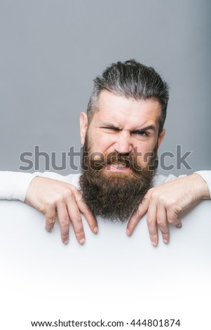 handsome bearded man with long lush beard and moustache on emotional face with white paper sheet in studio on grey background, copy space