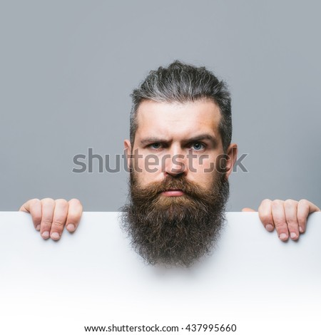 handsome bearded man with long lush beard and moustache on serious face with white paper sheet in studio on grey background, copy space