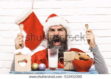 handsome bearded man with long snowy beard on angry face holding wooden spoons near christmas table in red santa suit on white brick wall background with sock on