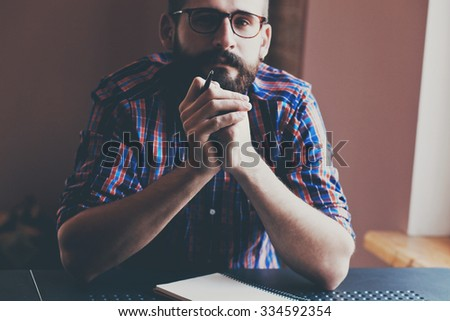 handsome bearded man with pen and notebook - stock photo