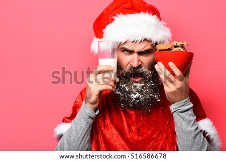 handsome bearded man with stylish mustache and long snowy beard on angry face holding glass of milk with chocolate chip cookies in red santa suit on studio background