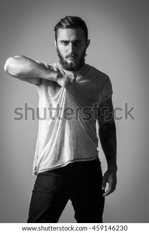 Handsome Bearded Man With Tattoo In Grey T-shirt Posing On Background. Model Tests - stock photo