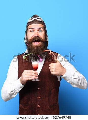 handsome bearded pilot or aviator man with long beard and mustache on smiling face holding glass of alcoholic shot in vintage suede leather waistcoat with hat and glasses on blue studio background