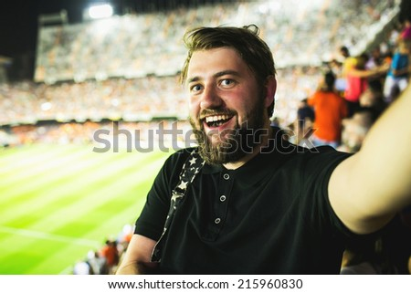 Handsome bearded supporter watching football game and making selfie self-portrait with smartphone at Camp Nou Stadium in Barcelona, Spain - stock photo