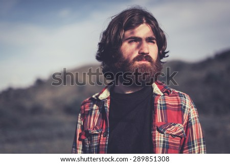 Handsome bearded young man standing staring into the sunset with a dreamy pensive expression, head and shoulders outdoors in the countryside - stock photo