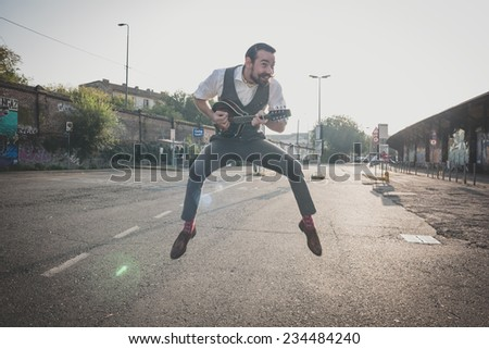 handsome big moustache hipster man playing mandolin in the city - stock photo
