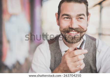 handsome big moustache hipster man smoking pipe in the city - stock photo