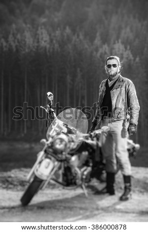 Handsome biker standing by his cruiser motorcycle on a sunny day with forest on the background. Man is wearing leather jacket and sunglasses. Vertical photo. Tilt lens blur effect. black and white - stock photo