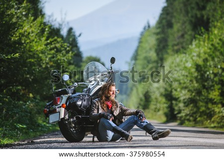 Handsome biker with beard and long hair sitting next to a traveler motorcycle on an open road. Guy is wearing leather jacket and blue jeans. Sunny summer day in the mountains. - stock photo