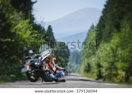 Handsome biker with beard and long hair sitting next to his custom made cruiser motorcycle on an open road. Guy is wearing leather jacket and blue jeans, looking into distance. tilt shift soft effect - stock photo