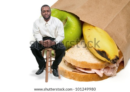 Handsome black African American man with a nutritious lunch in a brown bag. - stock photo