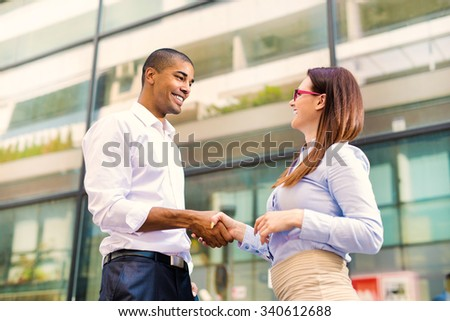 Handsome black man and his partner looking each other and smiling. They are shaking hands and they are happy hearing good news. Shallow depth of field. - stock photo