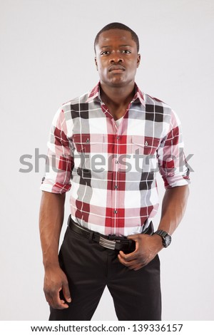 Handsome black man in a plaid shirt and bow tie, looking at the camera with a thoughtful and serious expression