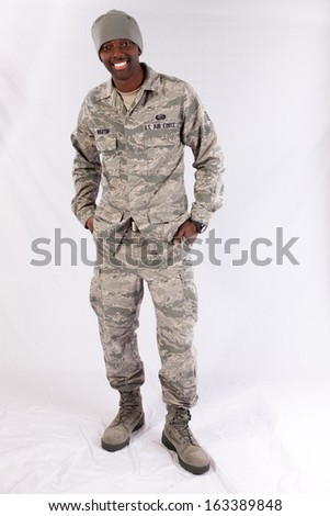 Handsome black man in a United States Air Force fatigues, looking at the camera with a happy expression with his hands in his pockets - stock photo